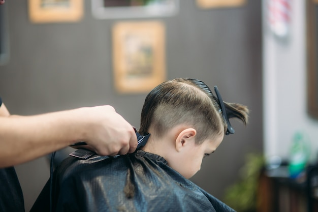 Little boy die kapsel door kapper krijgen terwijl het zitten als voorzitter bij herenkapper.