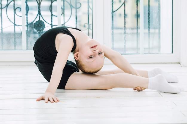 Little child girl gymnast doet zich het uitrekken in een lichte kamer op een vrolijke en schattige venster achtergrond