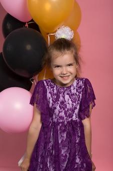 Little dark haired meisje met kleurrijke ballonnen op roze achtergrond