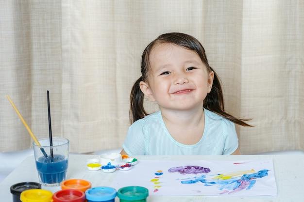 Little girl-glimlach schilderen met penseel en kleurrijke verven kinderen ontwikkeling concep