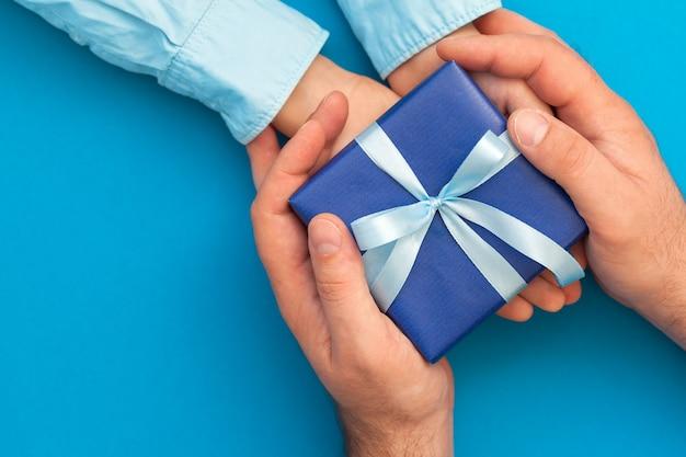 Little son geeft een geschenkdoos aan zijn vader