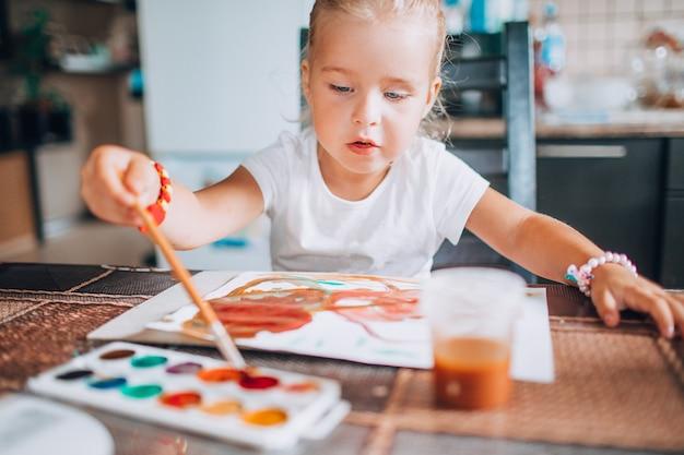 Littleirl schilderij met penseel en water kleuren in de keuken. kid activiteiten concept. detailopname. afgezwakt.