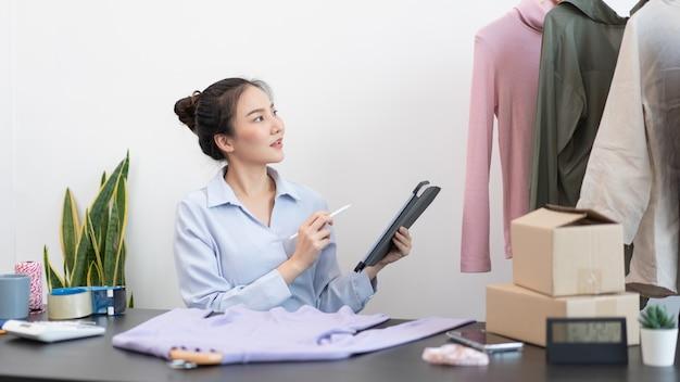 Live shopping concept een vrouwelijke dealer die een tabletpotlood gebruikt dat op de tablet veegt om de bestellingen van de dag te controleren.