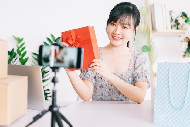 Live stream van jonge aziatische vrouw om geschenken te geven aan het publiek dat haar stream bekijkt op sociale netwerkplatforms