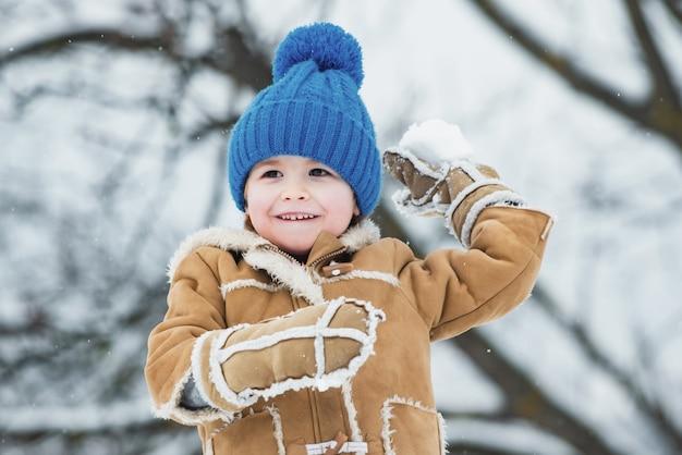 Llittle jongen die een sneeuwbal buiten gooit
