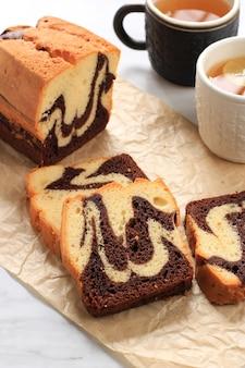 Loaf marble cake slice op witte marmeren achtergrond, geserveerd met thee. concept wit bakkerijproduct