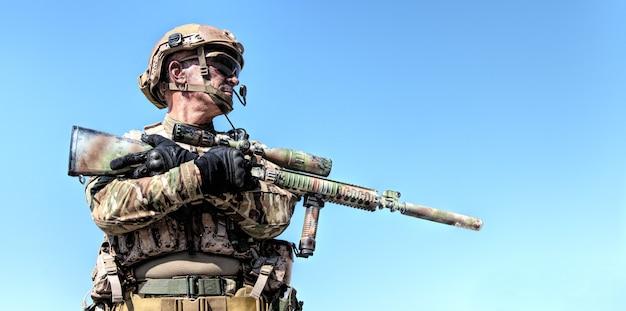 Locatie portret van special forces soldaat in velduniformen met wapens, portret op blauwe hemel
