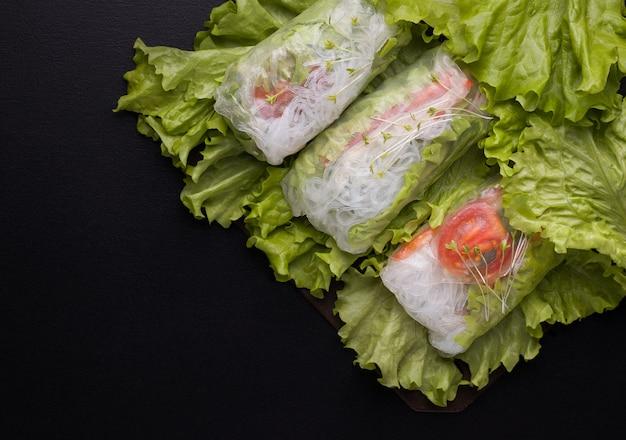 Loempia's met groenten in rijstpapier op zwart. kopieer ruimtes