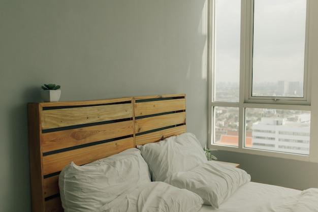 Loft houten hoofdeinde van dennenhout met wit bed.