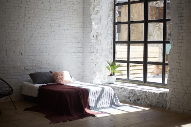 Loft slaapkamer interieur met grote ramen en lichte muren