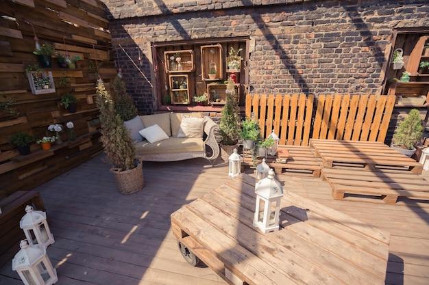 Loft tuinontwerp van veranda. houten versieringen. groene planten
