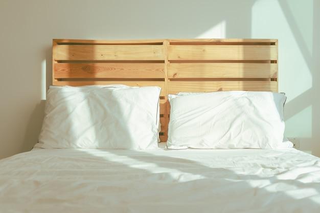 Loft witte slaapkamer met zacht zonlicht van winterochtend.