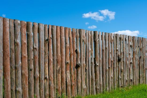 Log houten hek. de textuur van de oude houten omheining. houten vintage achtergrond.