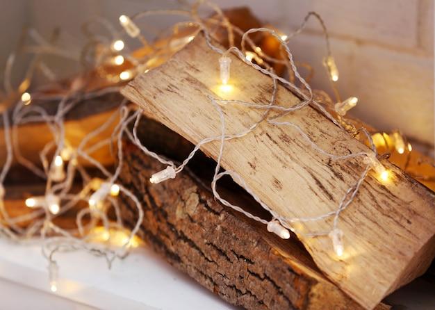Logboeken en lichten in decoratieve kersthaard, close-up