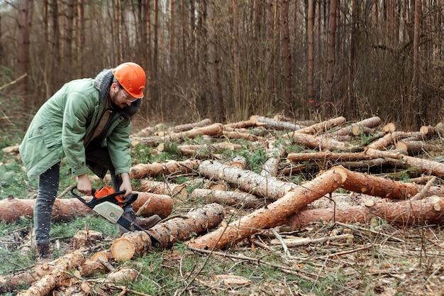 Loggen, werknemer in een beschermende pak met een kettingzaag hout zagen