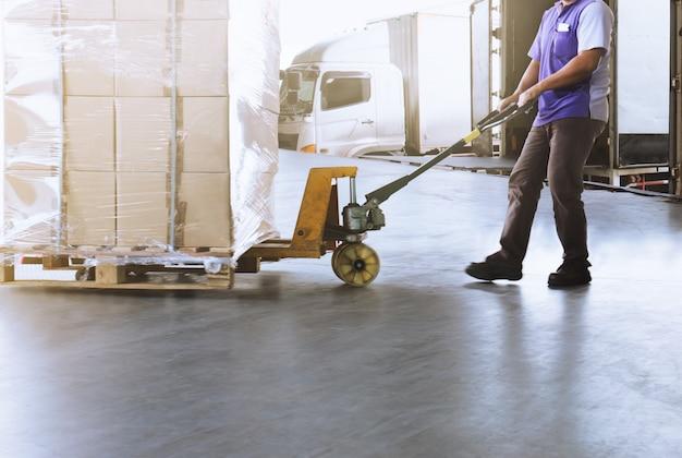 Logistiek en magazijn. vrachtwagenchauffeur die een pallettruck met de verzending sleept