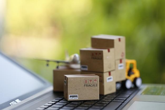Logistiek en vrachtvrachtconcept: vorkheftruck verplaatst een papieren doos op het toetsenbord van een notebook in de natuurlijke groene natuur. toont internationale vracht- of verzendservice voor online winkelen.
