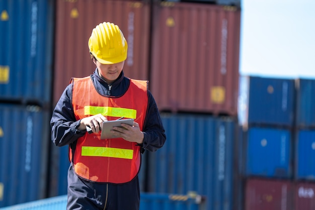 Logistiek engineer controle in de haven, containers laden voor vrachtwagens exporteren en logistiek importeren