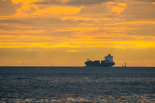 Logistiek import export container vrachtschip in zeehaven op avondrood, vrachtvervoer per containerschip boot