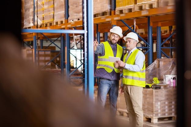 Logistieke vragen. aardige positieve man wijst naar de opslagplanken terwijl hij met de logistiek manager praat