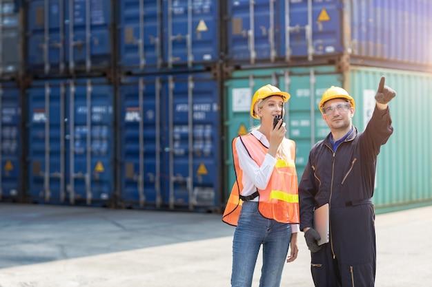 Logistieke werknemer man en vrouw werkteam met radiobesturing containers laden bij havenlading naar vrachtwagens voor export en import goederen.