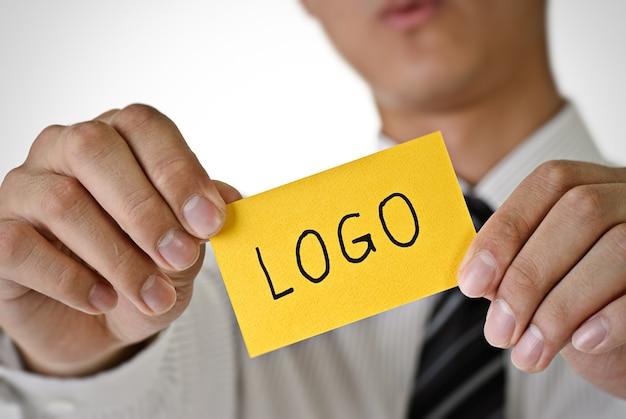 Logo woorden op gele kaart houden door zakenman