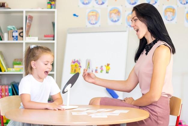 Logopedist leert het meisje de brief te zeggen