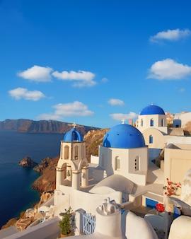 Lokale kerk met blauwe koepel in oia dorp, santorini-eiland, griekenland
