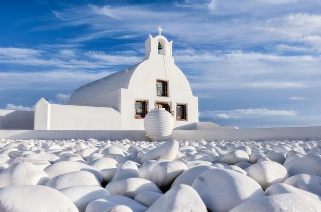 Lokale kerk met blauwe koepel in oia dorp, santorini, griekenland