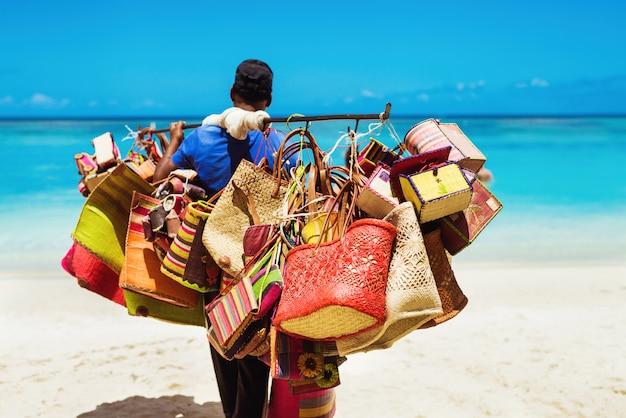 Lokale man die handgemaakte lederen tassen verkoopt, loopt langs heldere kust