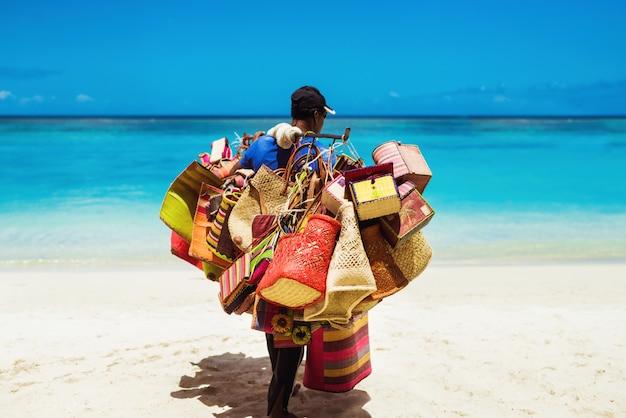 Lokale mannelijke verkoper die handgemaakte strandaccessoires verkoopt die aan zee werken