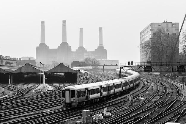 Lokale treinen en spoorlijnen verplaatsen in londen, met battersea power station achter de mist.