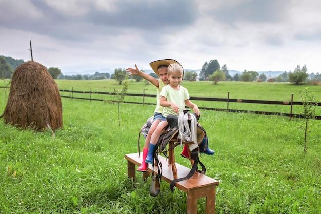 Lokale vakantie, blijf veilig, blijf thuis. kleine kinderen in cowboyhoed spelen in het westen op de boerderij tussen de bergen, gelukkige zomer op het platteland, kindertijd en dromen