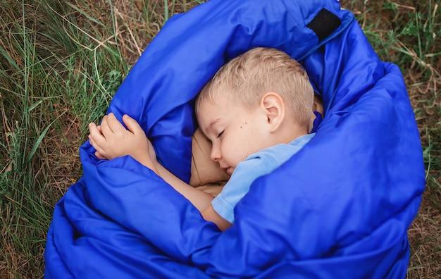 Lokale vakantie. leuke jongen die rust heeft en alleen droomt in de slaapzak op de top van de berg