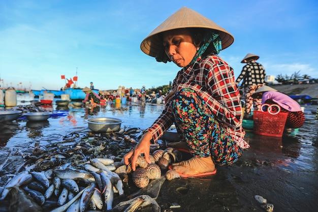 Lokale verkoper verzamelt vissen en schelpen in het beroemde vissersdorpje mui ne, vietnam