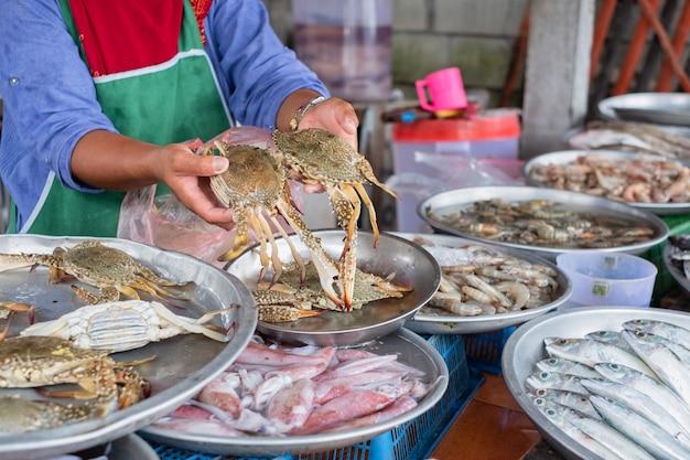 Lokale zeevruchtenverkoper houdt en toont twee grijpers. lokale zeevruchtenwinkel in thailand.