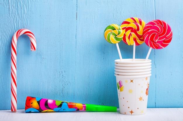 Lollies in cups met riet van het suikergoed en fluit op blauwe houten muur