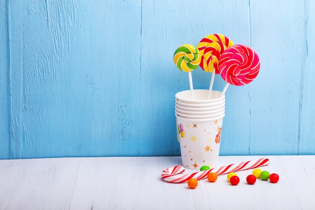 Lollies in cups met snoep stokken op blauwe houten muur