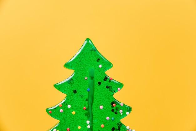 Lollipop in de vorm van een kerstboom close-up op een gele.