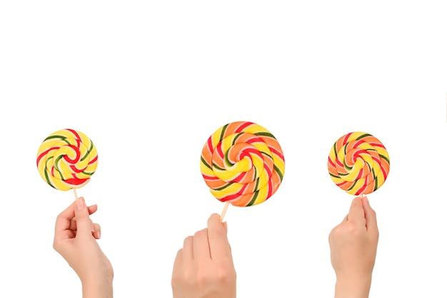 Lollipop in vrouwelijke hand geïsoleerd op een witte achtergrond. ruimte voor tekst of ontwerp.