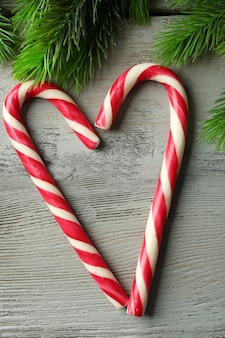 Lollipop snoepjes zoals hart met dennenboomtakken op houten oppervlak
