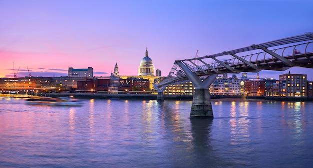 Londen bij zonsondergang, millenniumbrug die naar verlichte st. paul kathedraal over de rivier van theems leidt