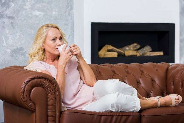 Long shot blonde dame die een kopje koffie drinkt