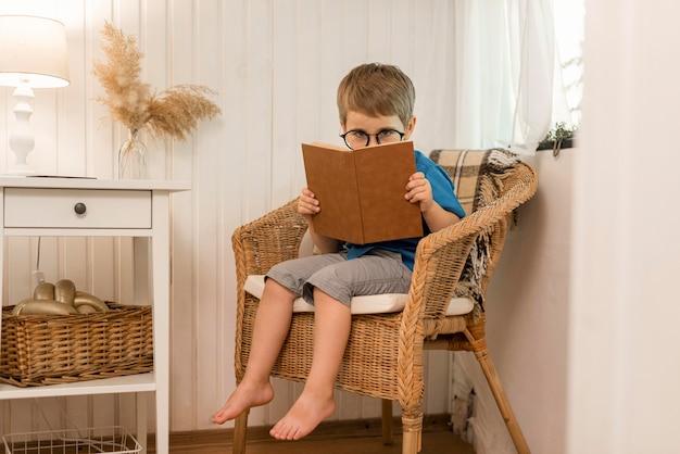Long shot jongen lezen in een fauteuil