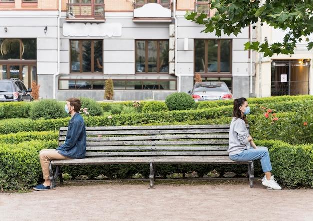 Long shot mensen die de sociale afstand respecteren terwijl ze op een bankje zitten