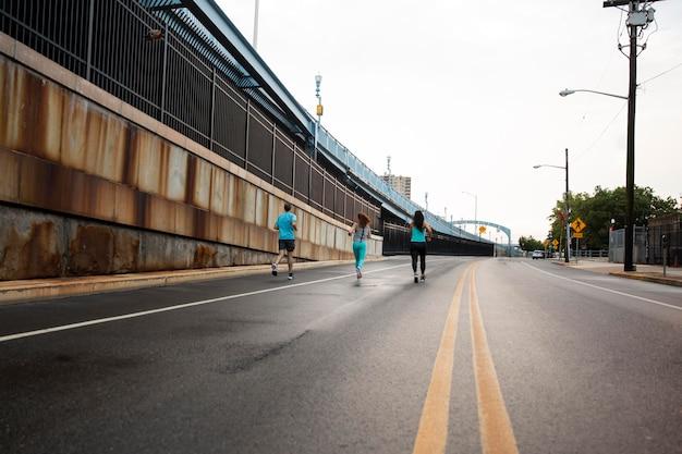 Long shot mensen die op straat rennen