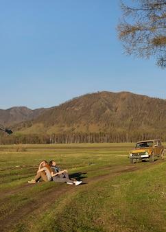 Long shot mensen die samen op het gras zitten
