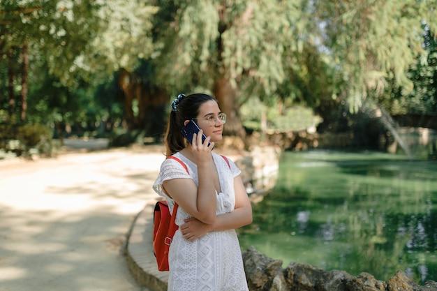 Long shot van een jonge vrouw met een witte jurk en een rode rugzak die aan de telefoon praat in een park