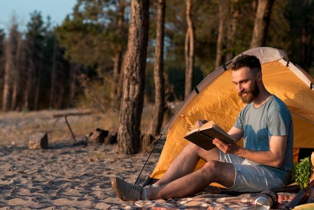 Long shot van man die een boek leest bij de tent
