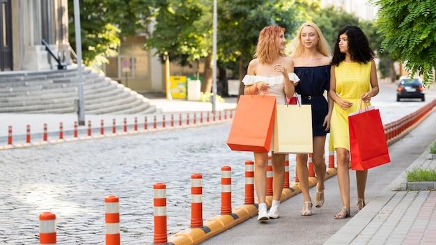 Long shot van mooie meisjes met boodschappentas